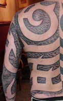 Negative Tribal Back Tattoo